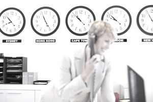 World clocks behind businesswoman in office