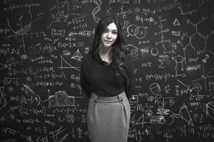 Professional woman standing in front of a chalkboard with complex equations.