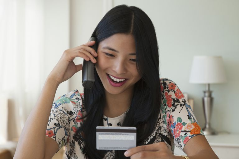 A woman holds a credit card while talking on the phone