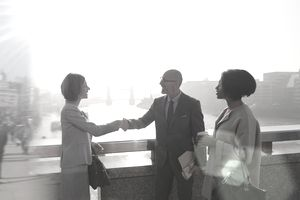 Silhouette business people handshaking on sunny urban bridge over Thames River, London, UK