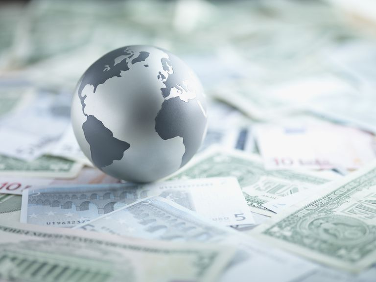 Metal globe resting on paper currency