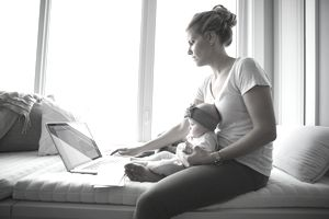 woman using laptop on bed while holding baby