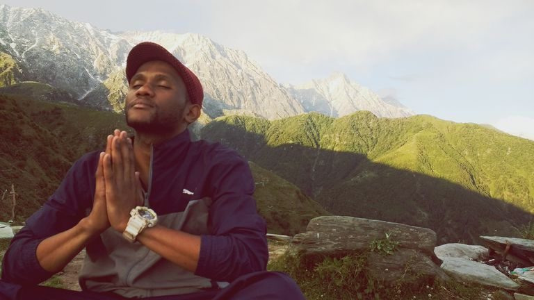 Low Angle View Of Young Man Meditating In Prayer Position On Mountain