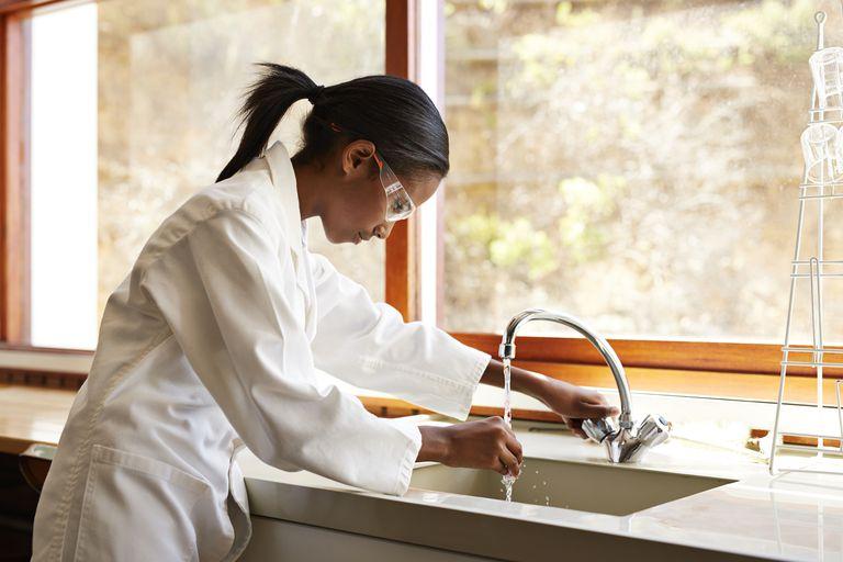 Girl washing glass instrument en science class