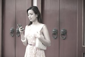 Young woman holding up a phone in front of red doors.