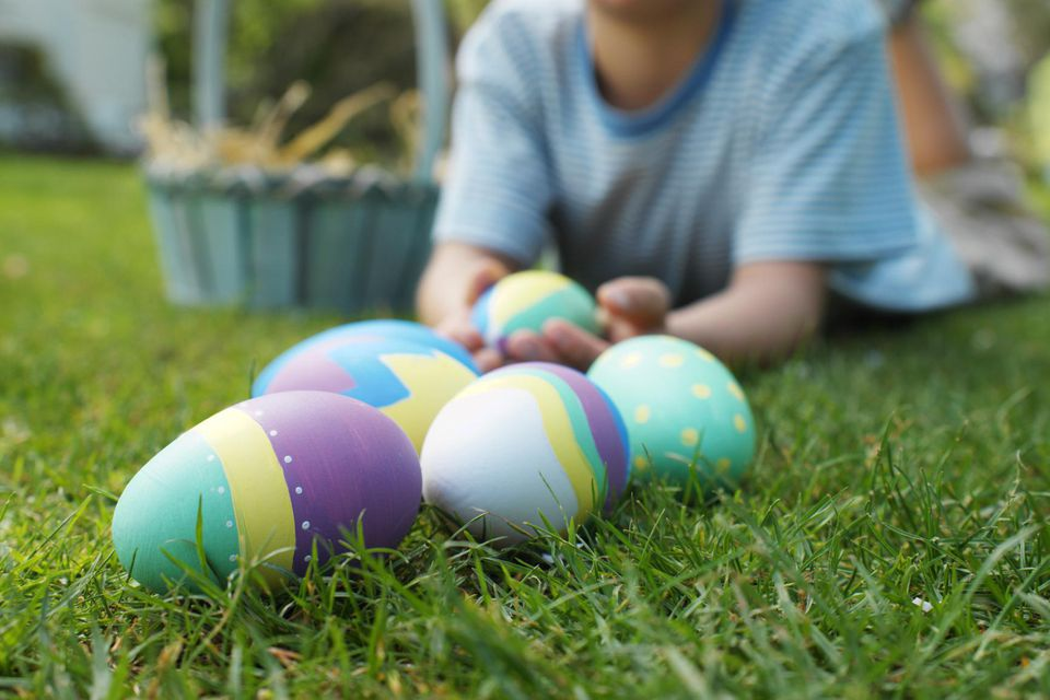 Boy (7-8) lying on lawn with Easter eggs