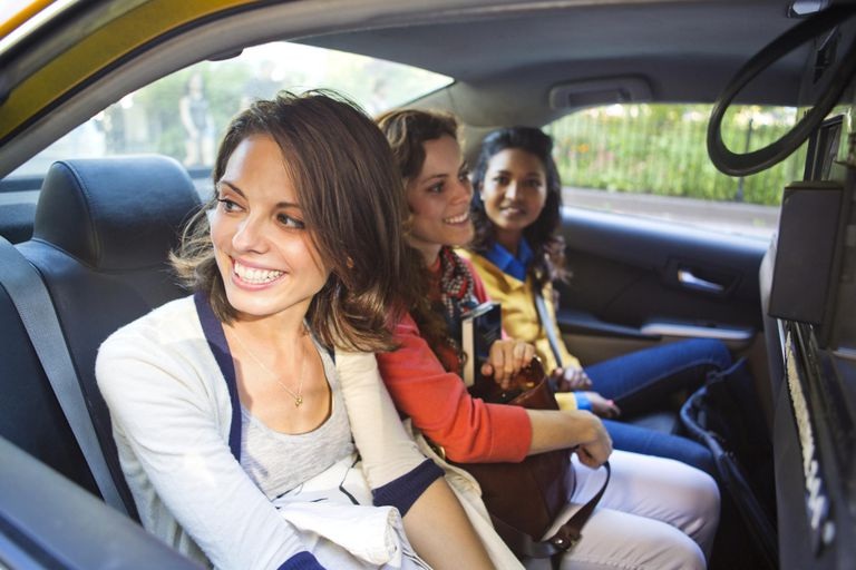 Three Female Friends Sharing a Taxi Cab Together