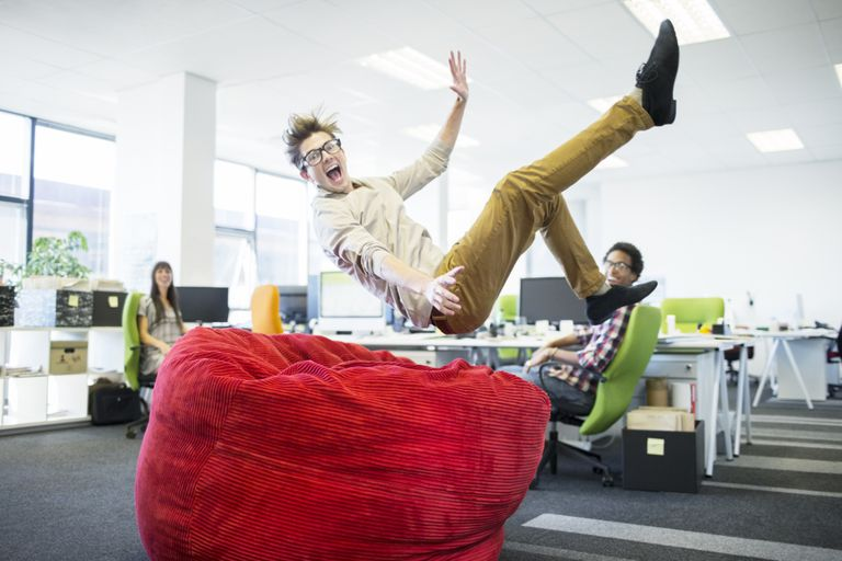 Businessman jumping into beanbag chair in office