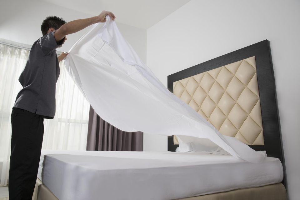 male housekeeper in hotel throwing sheet on bed