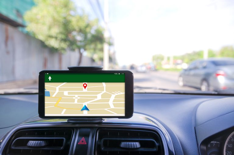 Close-Up Of Smart Phone Displaying Map On Dashboard Of Car