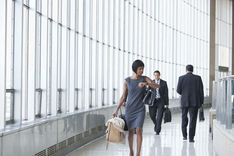 Black businesswoman checking the time on wristwatch in corridor