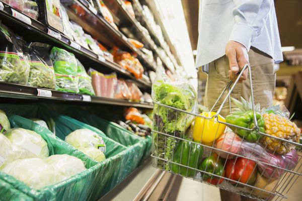 man with basket full of produce at grocery store