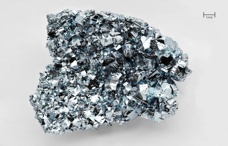 These are crystals of the metal osmium. At room temperature, the density of osmium is about 22.6 grams per cubic centimeter, making it (along with iridium) the most dense known element.