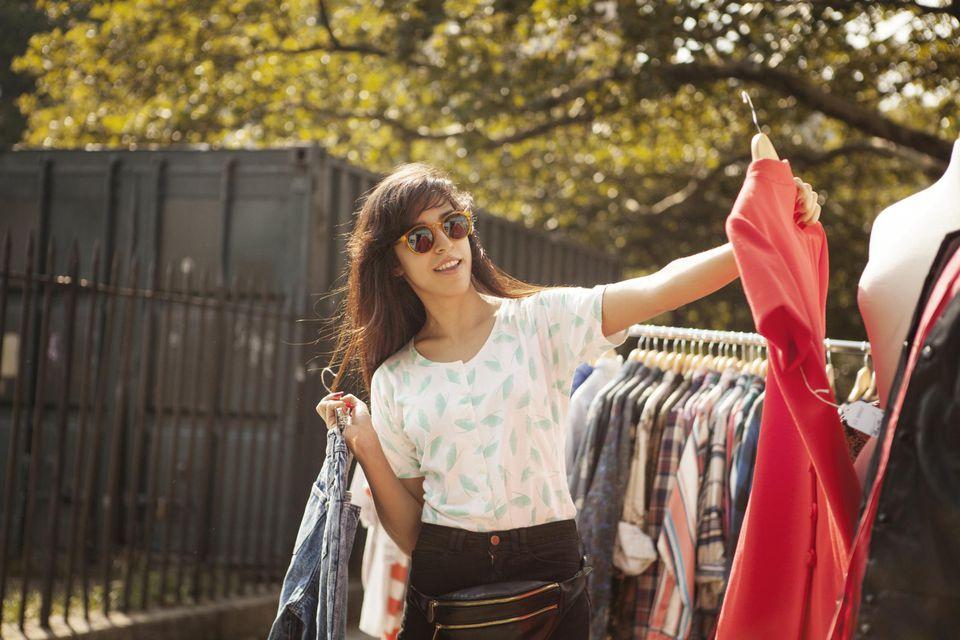 Hip Woman Looking at Red Dress at Vintage Shop