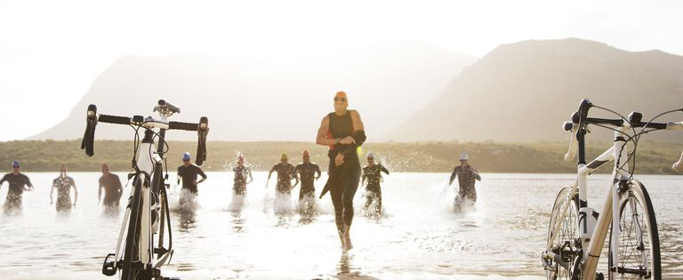 Triathletes running to bicycles on beach