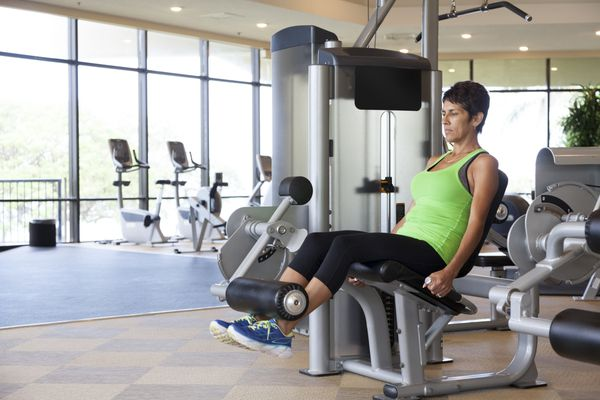 Woman doing leg extensions at the gym