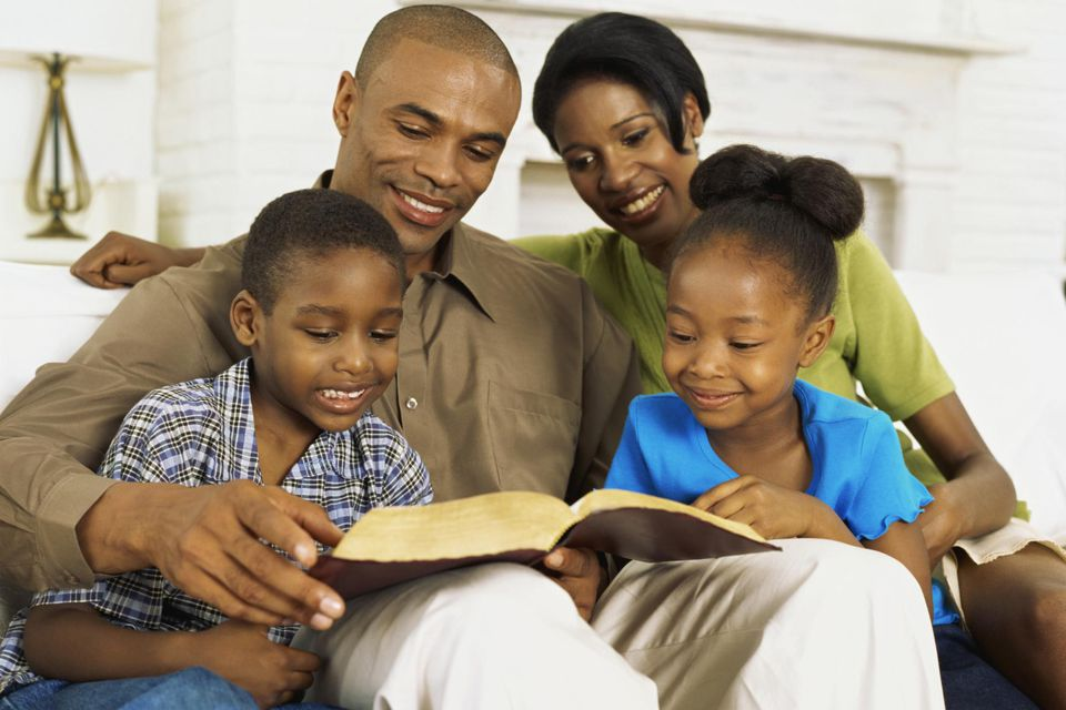 Parents and their children reading the bible.