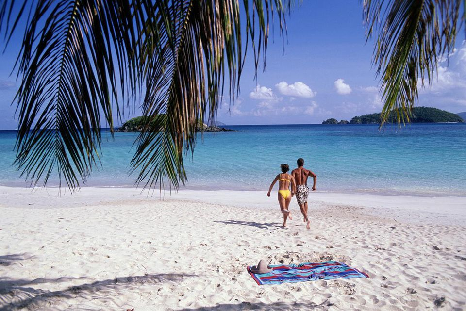 Couple running on beach, Cinnamon Bay, St. John, US Virgin Islands