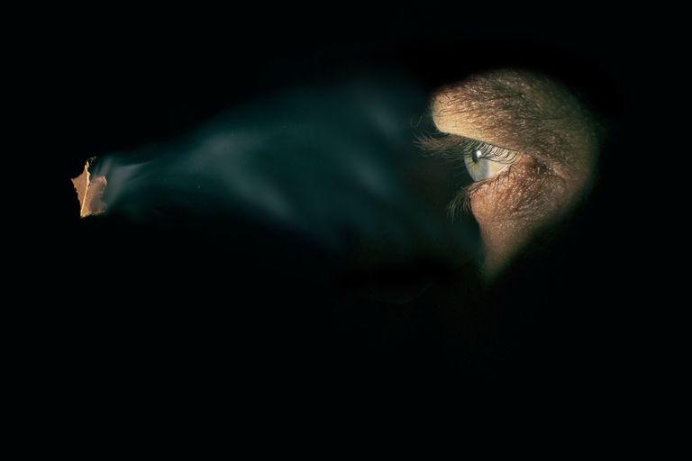 Man looking through a keyhole.