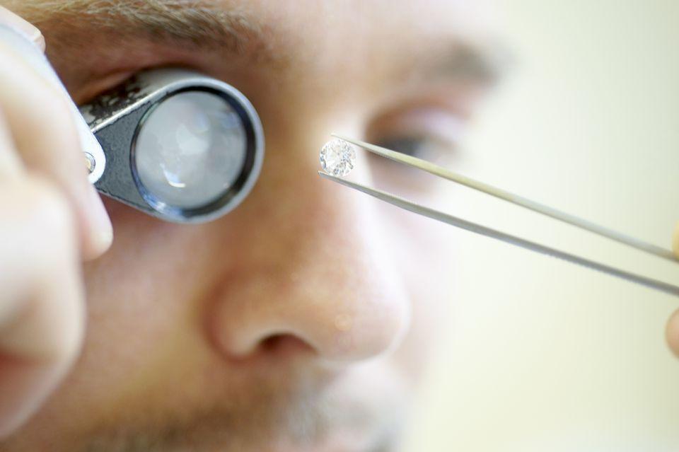A man examining a diamond with a jewler's loupe