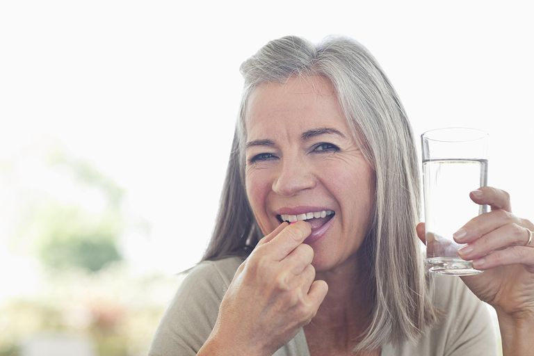 Woman taking supplement with water.