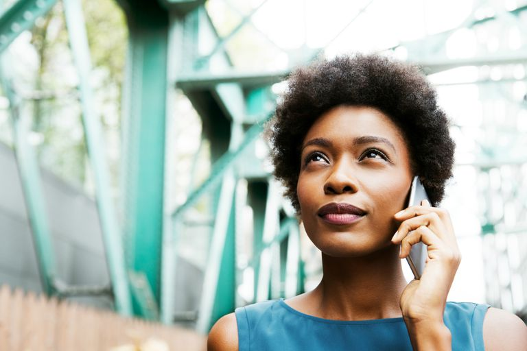 Woman talking on the phone on a bridge