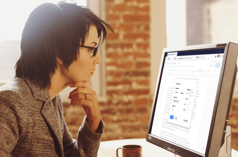 Woman looking at computer screen with Google Docs open