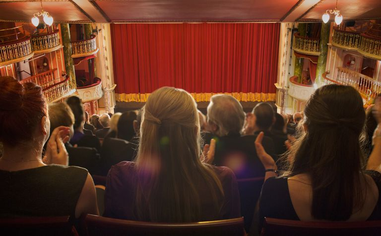 Audience clapping in theater.