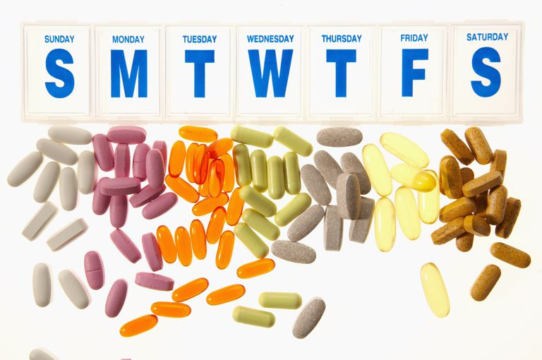 pill box with days of the week labels and groups of loose pills