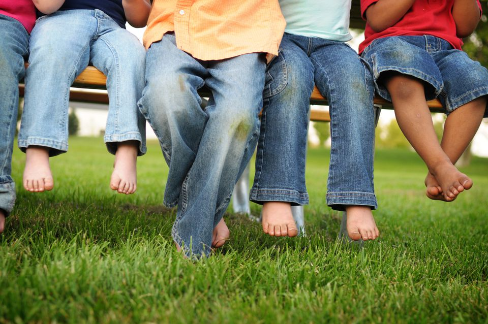 Grass Stained Pants and Feet of Children Sitting on a Bench