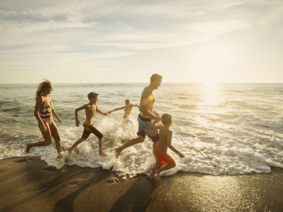 USA, California, Laguna Beach, Family with three children (6-7, 10-11, 14-15) running on beach
