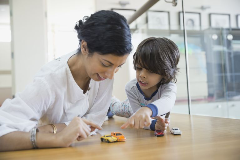 woman and son pointing at toy cars