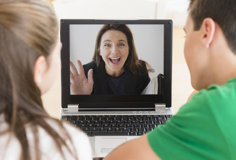Caucasian children video conferencing with mother on laptop