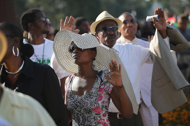 Black mourners gather to honor the life of Michael Brown killed by officer Darren Wilson in Ferguson, MO.