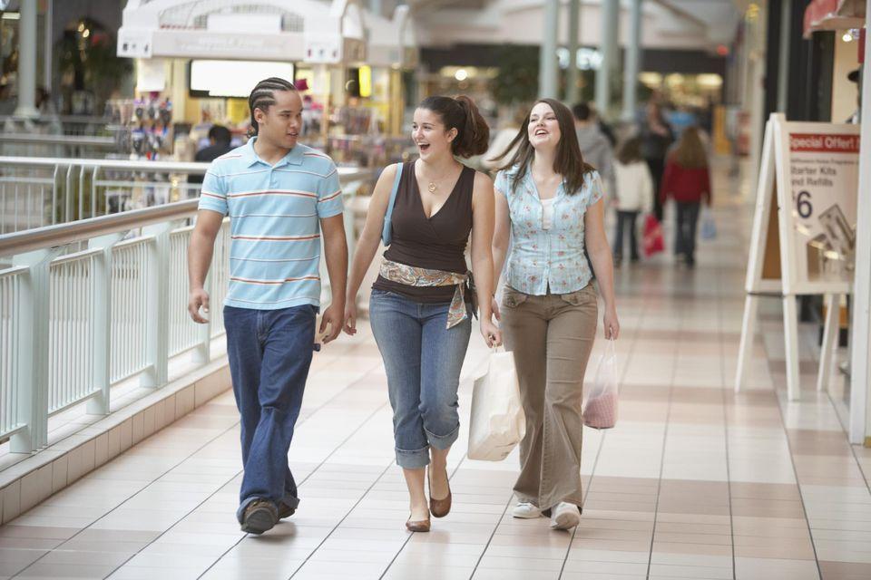 Two teenage girls and a teenage boy walking