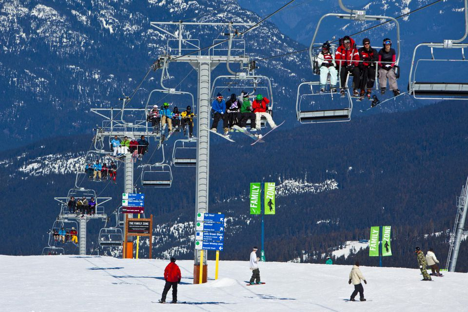 Skiers and snowboarders on chairlift and slopes, Whistler Blackcomb Ski Resort, Whistler, BC, Canada.