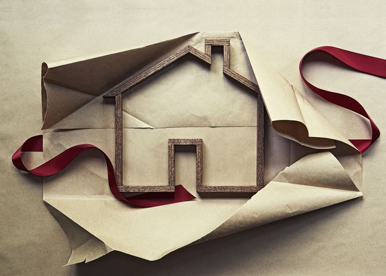 Wooden house frame in wrapping paper