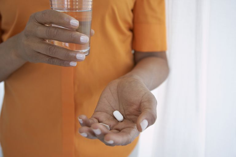 woman's hands holding pill and water glass