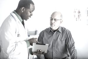 Physician assistant or doctor talking to patient in office