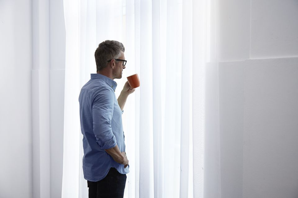 Businessman staring out of the window thoughtfully