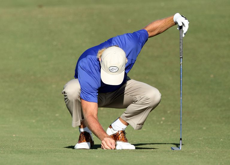Greg Norman of Australia moves a loose impediment from behind his ball.