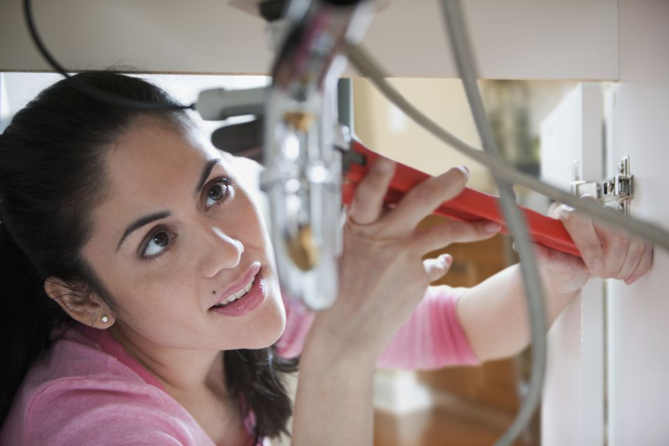 Mixed race woman fixing pipe with wrench