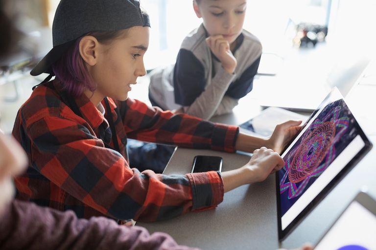 Pre-adolescent boys using digital tablet in classroom.