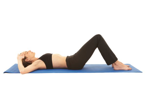 A woman performs the pelvic tilt exercise.