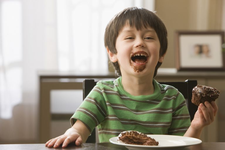Young child eating cake and acting on the pleasure principle