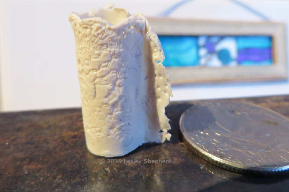 Dollhouse miniature of an embossed slab built porcelain vase, made in polymer clay.