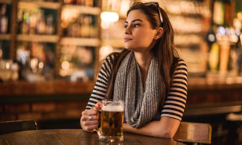 Lonely young woman sitting in a bar and thinking.