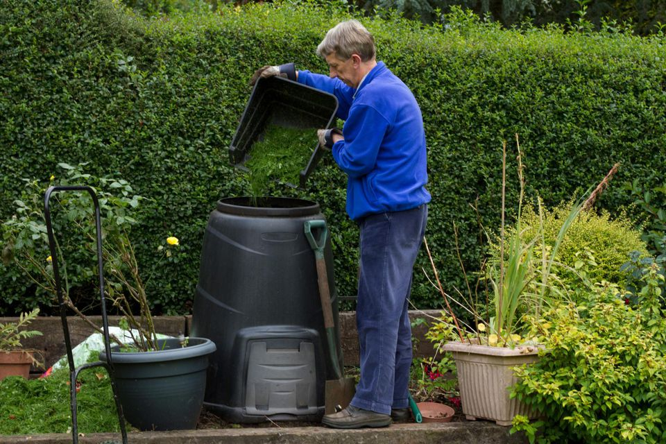 Man filling compost bin in garden