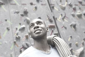 Man with rope standing below rock climbing wall