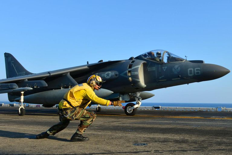 Aviation Boatswains Mate 3rd Class Cesar Salinas launches an AV-8B Harrier jet aircraft, assigned to the
